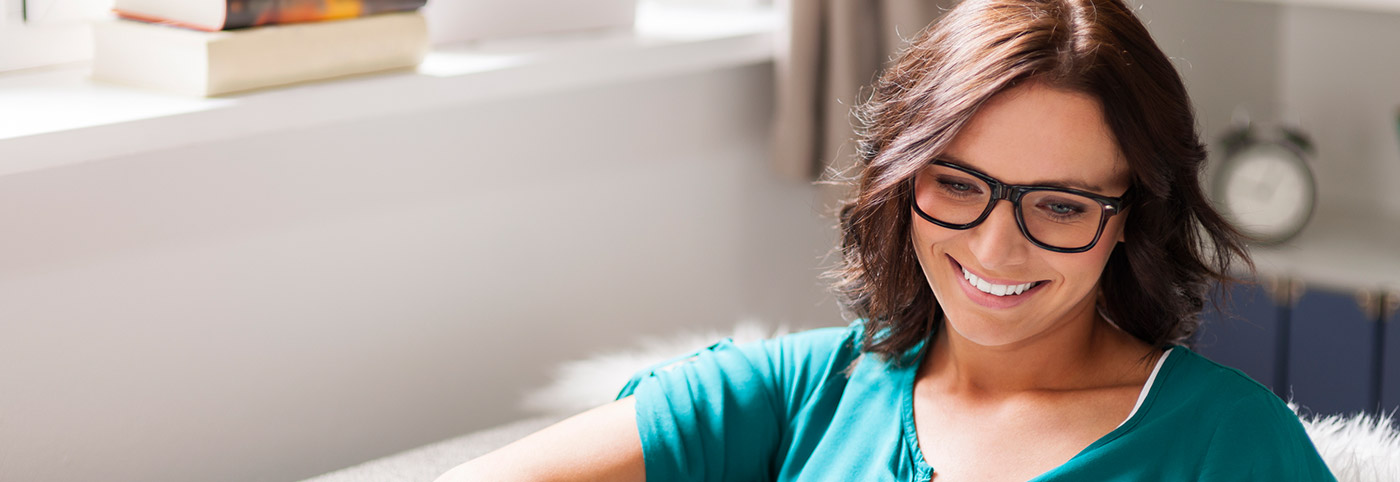 lady sporting glasses in teal blouse grinning