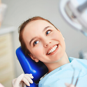 Female patient in dental chair smiling at dentist