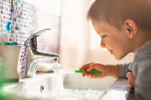 Young boy holding toothbrush under running water