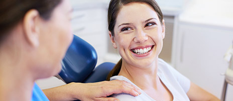 Happy patient in dental chair smiling jovially