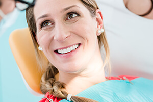 lady in dental chair smiling with picture-perfect teeth