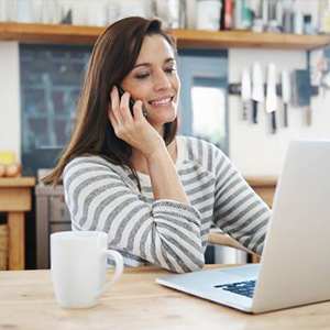 Smiling woman on phone looking at laptop