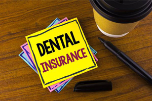 Dental insurance written on post card next to cup of coffee