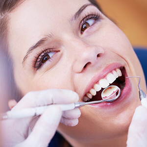 Lady in dental chair smiling at dentist