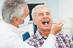 Older male patient being examined by dentist