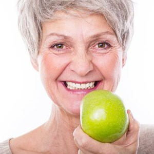 Older woman eating a green apple