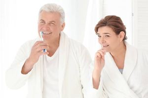 Older man and woman brushing teeth