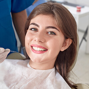 Young lady relaxing on dental chair smiling