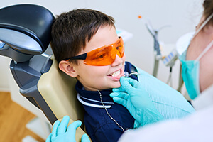 young boy with sports shades examined by dentist