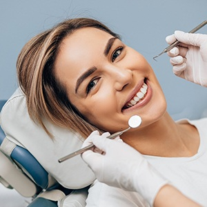 Smiling woman in dentist's chair receiving treatment