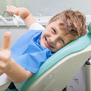 Young boy giving thumbs up in dental chair