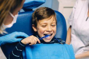 little boy brushing teeth in dental chair