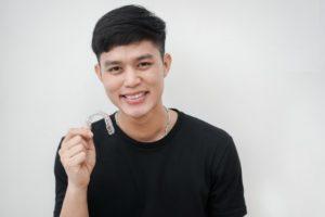 smiling man holding a SureSmile clear aligner